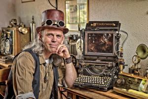 """""""Steam-Punk"""" Daniel Tännler bei sich zu Hause, mit einer alten Schreibmaschine mit digitalem Display, Sennhof, 21.6.2014, Steampunk ist ein Phänomen, das als literarische Strömung in den 1980ern begann[1] und sich zu einem Kunstgenre,[2] einer kulturellen Bewegung,[3] einem Stil und einer Subkultur ausgeweitet hat.[4] Dabei werden einerseits moderne und futuristische technische Funktionen mit Mitteln und Materialien des viktorianischen Zeitalters verknüpft, wodurch ein deutlicher Retro-Look der Technik entsteht. Andererseits wird das viktorianische Zeitalter bezüglich der Mode und Kultur idealisiert wiedergegeben. Steampunk fällt damit in den Bereich des sogenannten Retro-Futurismus,[3] also einer Sicht auf die Zukunft, wie sie in früheren Zeiten entstanden sein könnte.© Dominique Meienberg"""